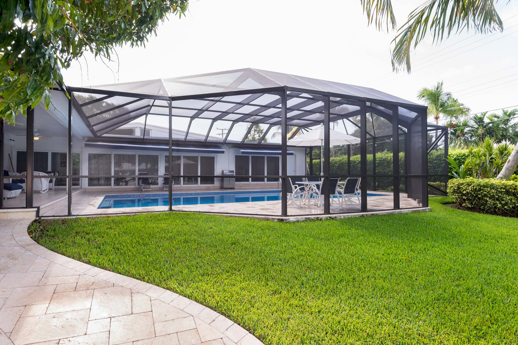 Pool-Enclosure-with-Mansard-Roof-and-Bronze-framing-on-a-beautiful-waterfront-home.